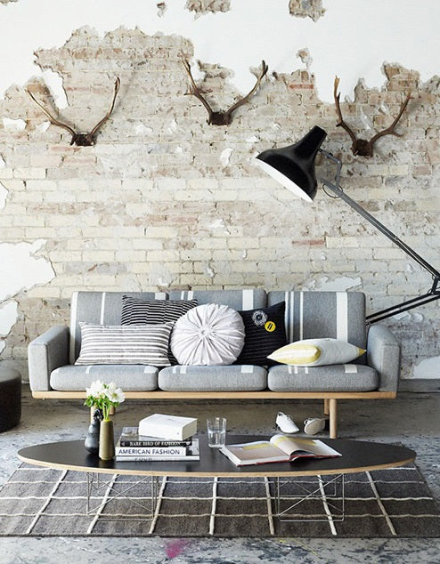 Rustic living room interior with exposed brick and crumbling paintwork, with grey sofa and oval coffee table
