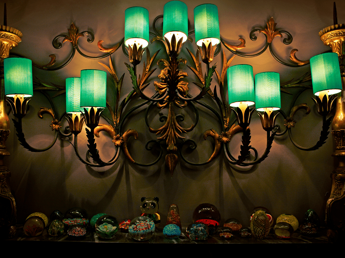 Ornate light fixtures with green lamp shades, in a dimly lit room