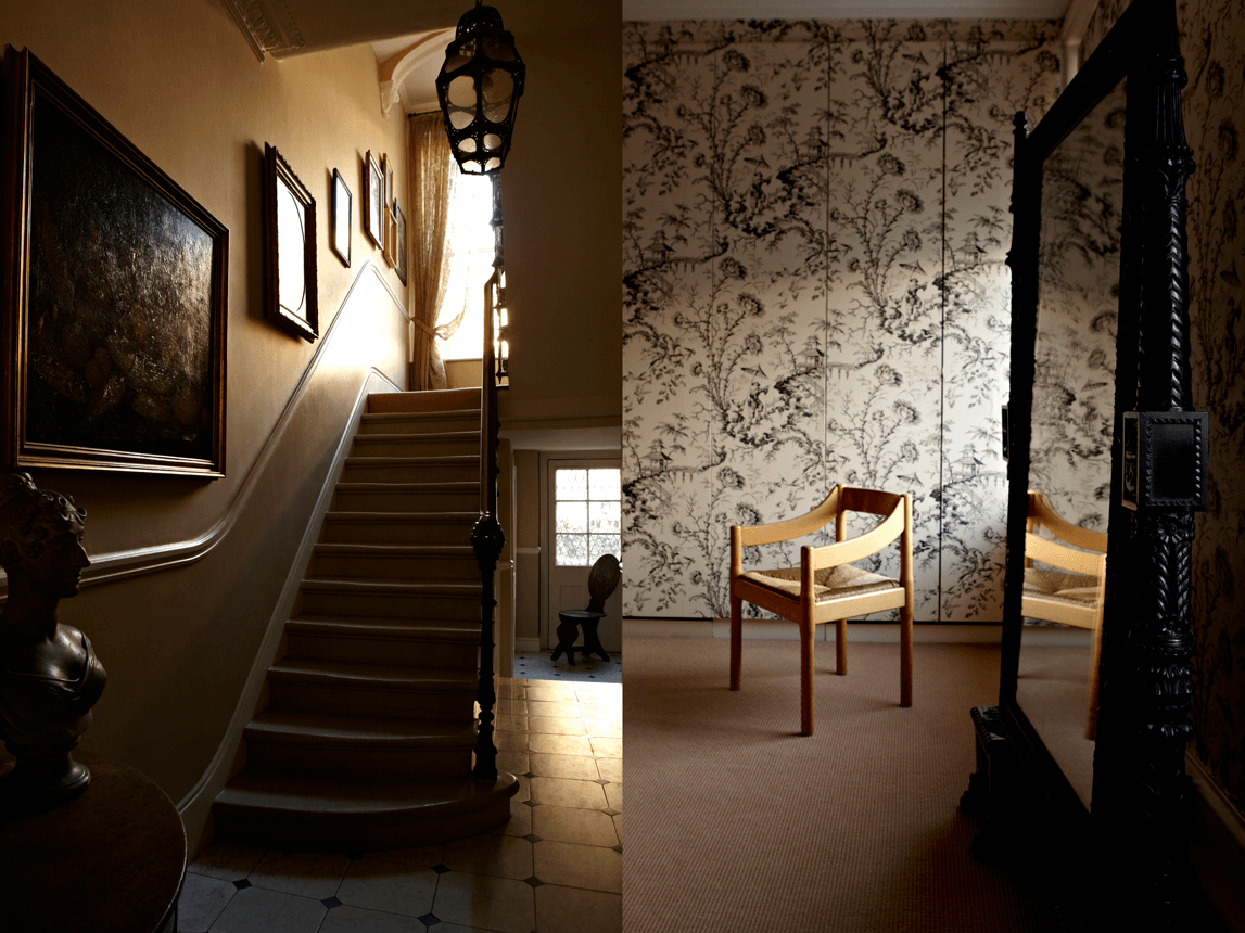 Dimly lit hall and a wooden chair in front of black and white floral wallpaper