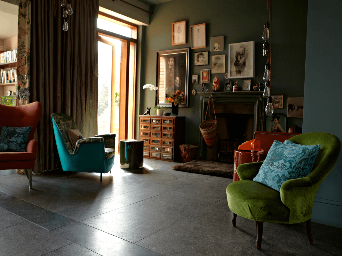 Dark and dimly lit living space, with dark ceramic tiled floors and ornate and traditional furniture