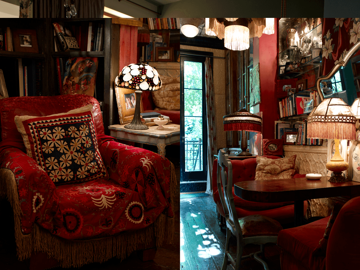 Dimly lit living space with red arm chair and small dining table, with red seats