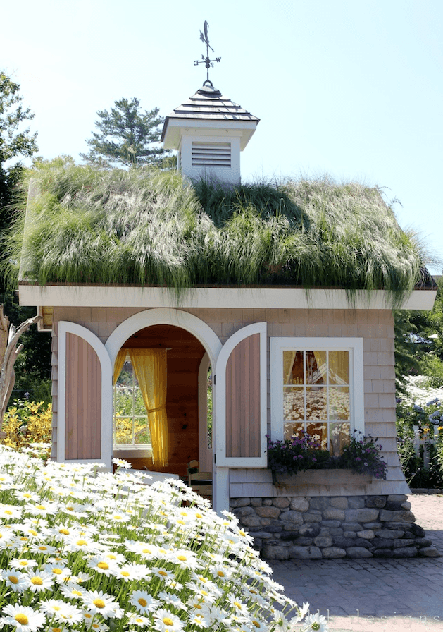A beach style playhouse with grass on the roof