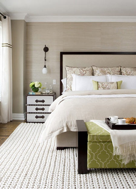 Modern bedroom with cream and white bedding and green footstool at the bottom of the bed