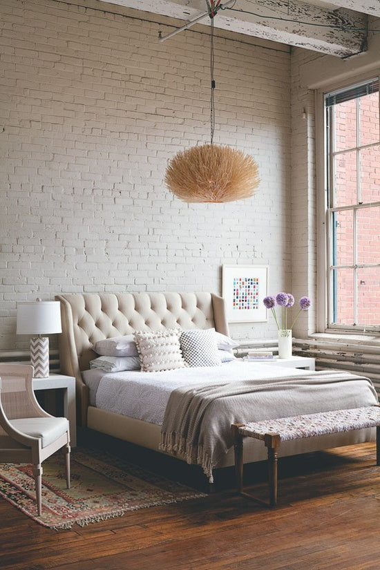 Trendy industrial bedroom with wooden floors, exposed cream bricks and distressed ceiling beams