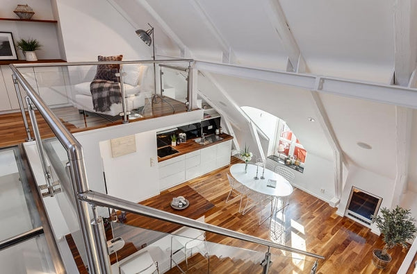 White loft space with wooden floors, looking down a flight of metal and glass stairs to a dining room