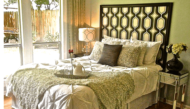 Black and gold hexagon patterned headboard behind a double bed