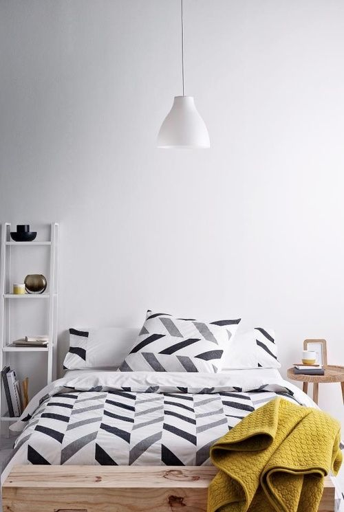 White ceiling lampshade above a bed with black, white and grey geometric bedding