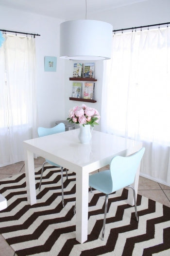 Black and white zig zag rug under an small white dining table