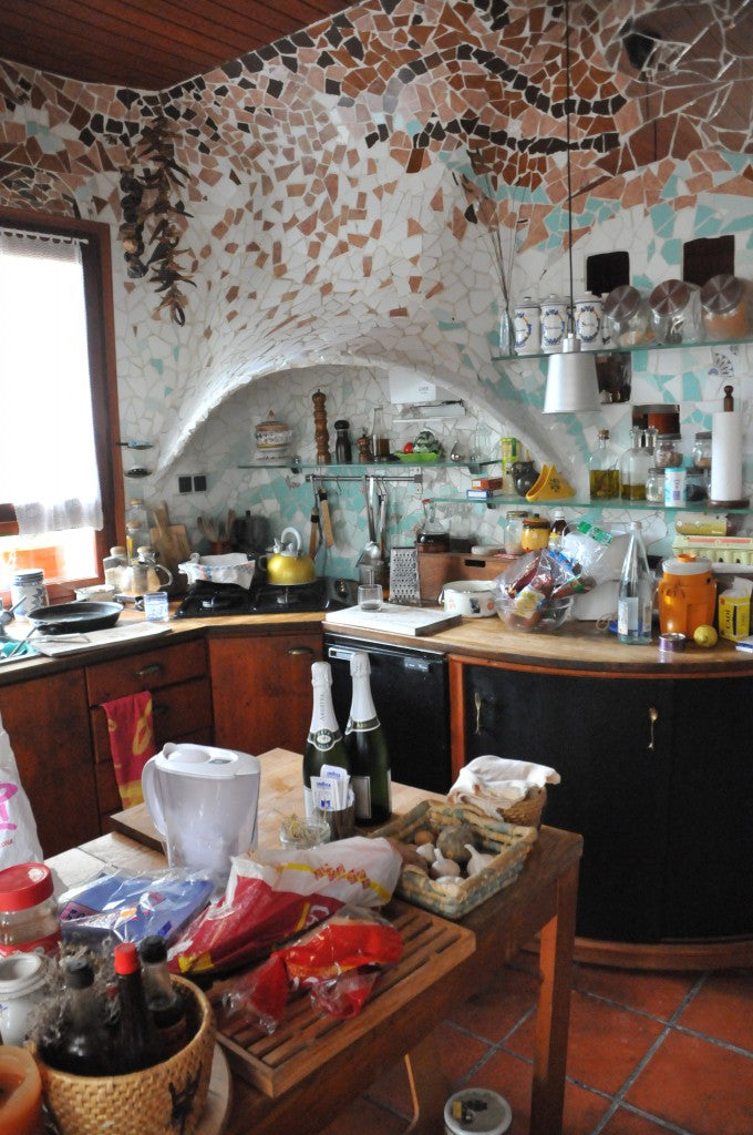 Funky Gaudi style kitchen with sloping curved walls and irregular brown and white tiles