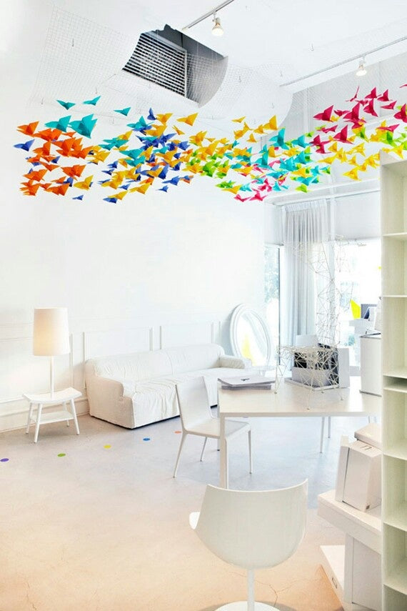 Very white living space, with orange, yellow, blue and pink paper butterflies hanging from the ceiling