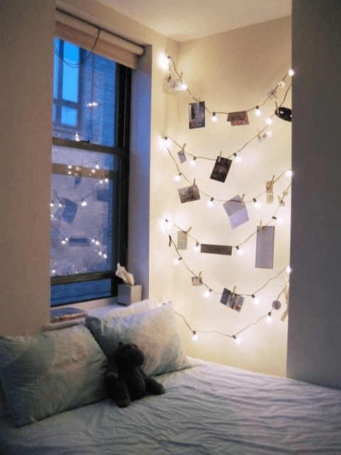 Cosy bedroom with double bed and fairy lights and pictures in alcove