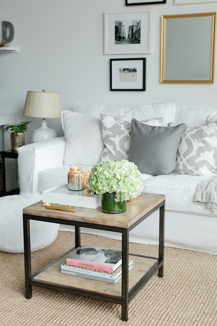White and cream living room with plants on a wooden coffee table