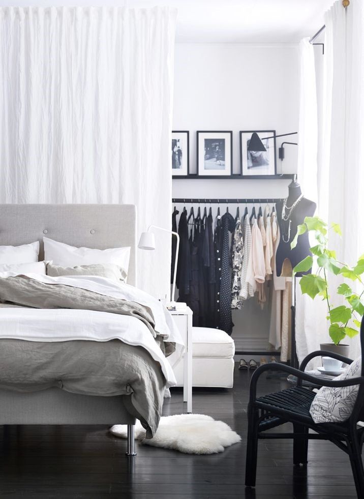 Grey double bed in front of a curtain, that is obscuring a rail of clothes