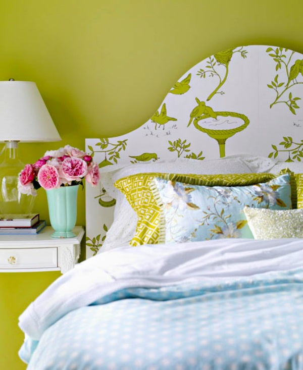 Light green wall colour with a bed and headboard in a matching colour, with a white print and bird design on it