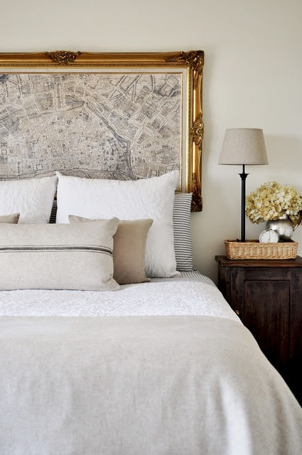 Cream bedroom and bedding with framed map as a headboard