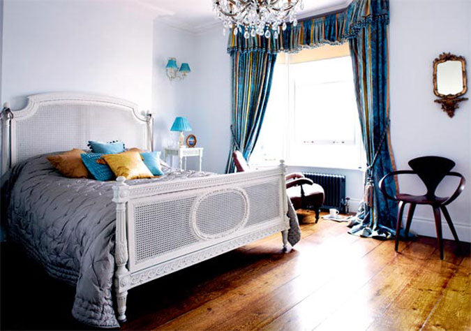 Hardwood floor in a bedroom with light blue walls and a double bed