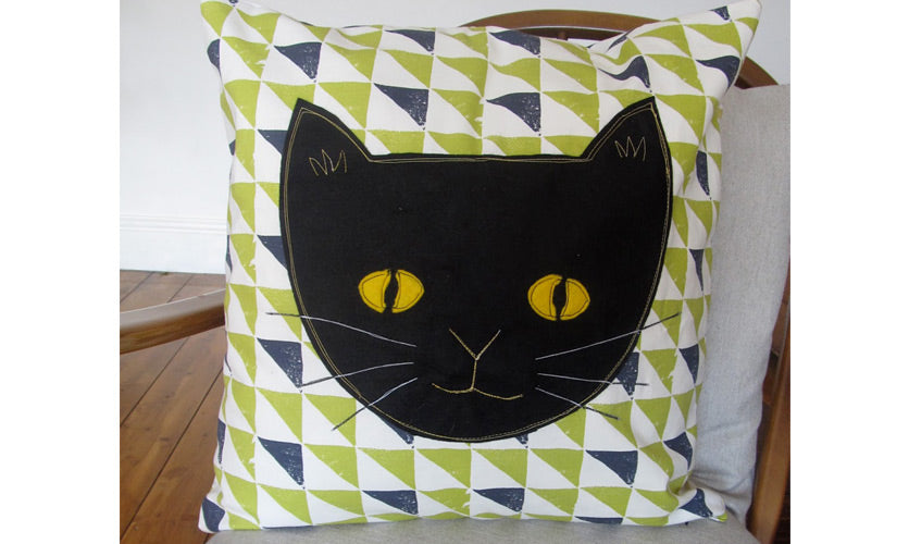 Black cat design on a white green and blue geometric triangle patterned cushion