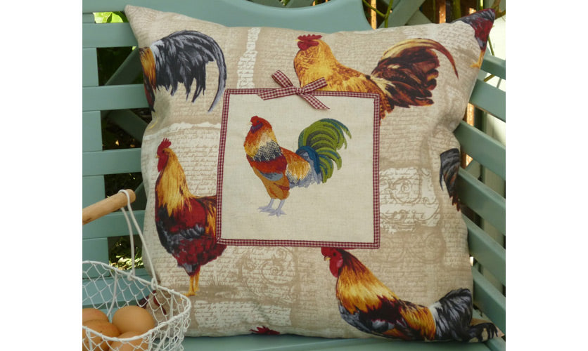 Beige rooster farmhouse cushion on a green bench