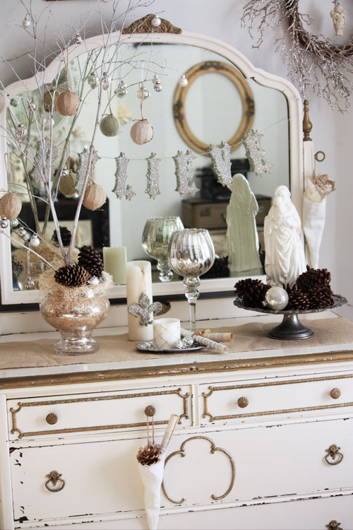 Rustic white and gold Christmas accessories on a shabby chic set of cream drawers