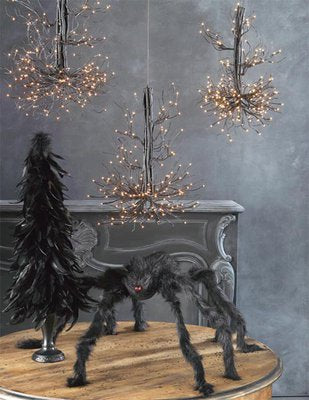 Fairy lights hanging from the ceiling of a black room, with big hairy black spider on the table