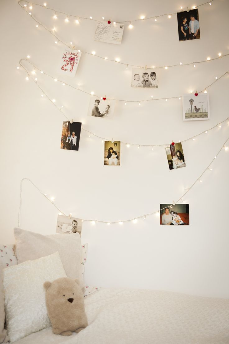Cream bedroom with fairy lights draped over the walls decorating personal photos