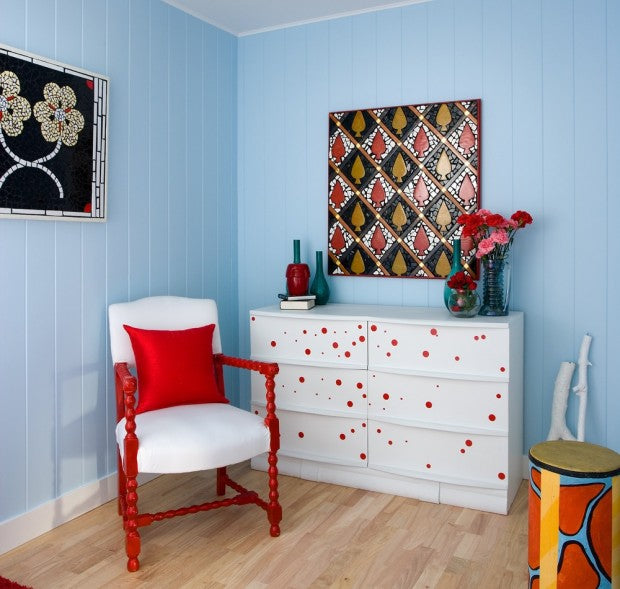 Light blue wood panel room with white drawers covered in red dots