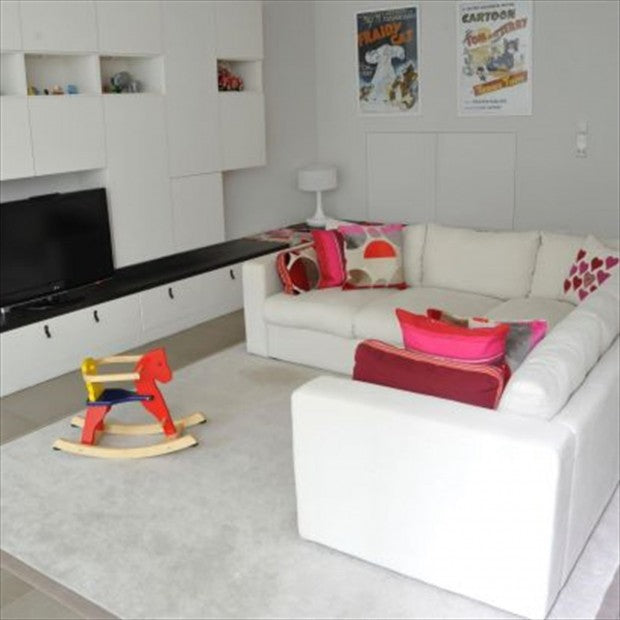 White living space, with white fitted media centre unit and white corner sofa