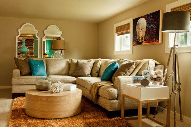 Cosy and warm beige living space with beige corner sofa covering in matching cushions as well as darker brown and teal cushions