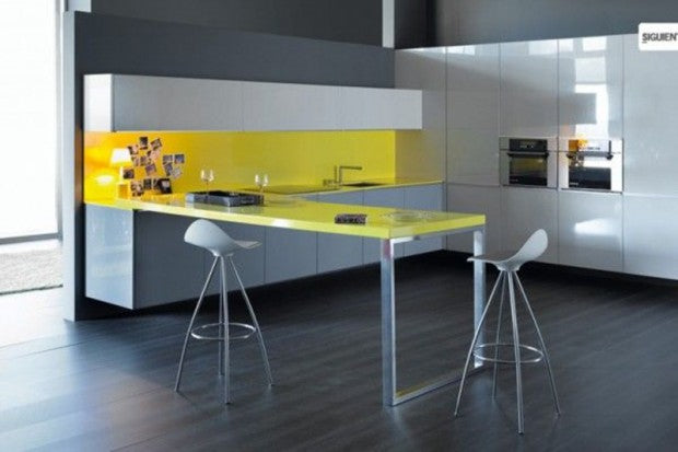Grey kitchen, with yellow backsplash and yellow breakfast table protruding out of the units