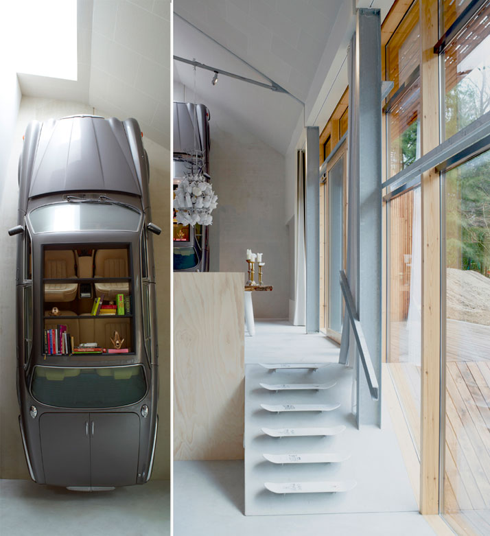 A grey sports car suspended upright on the side of a wall, with shelves and storage accessible within the interior