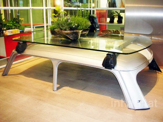 Glass coffee table mounted to the top of a mini roof, which act as table legs