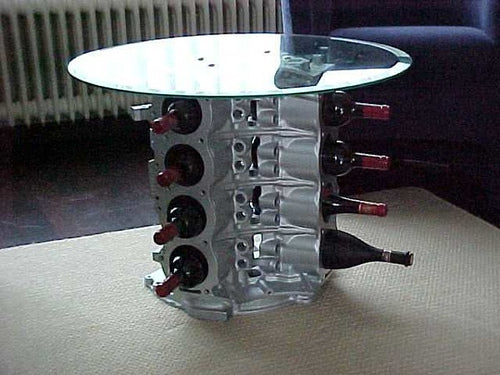 Glass top coffee table with a metal base for storing wine bottles, made from an engine