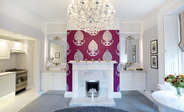 White living space with white fireplace on a dark maroon chimney wall
