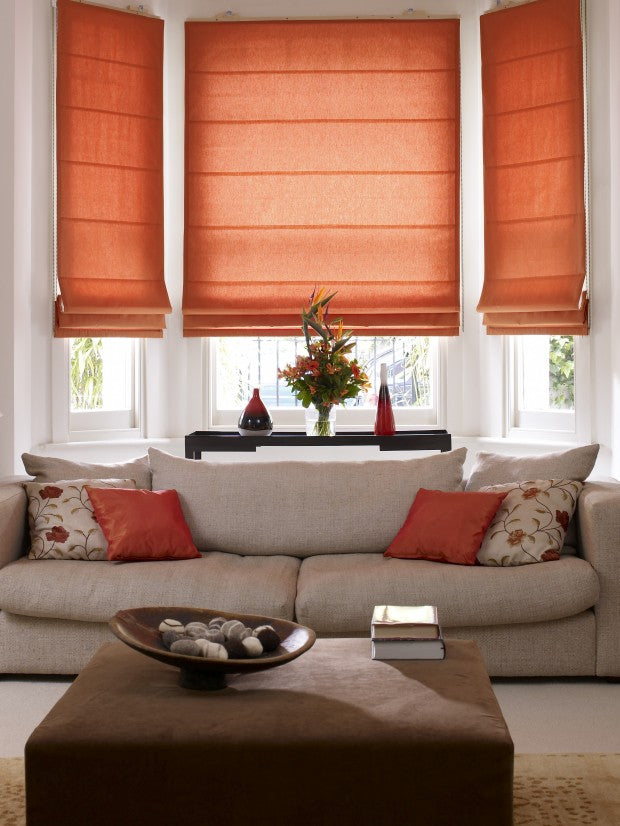 Warm red roman blinds in a living room bay window, with beige sofa and red cushions