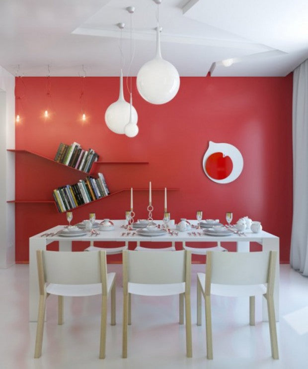 Dining room with white table and feature wall that is solid red with sloping floating bookshelves