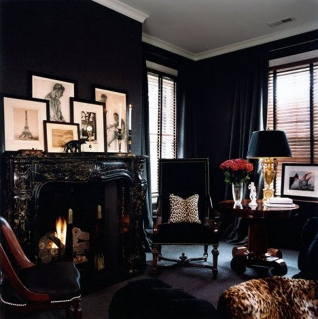 Black living room with intricate black fireplace, classy gold table lamp and faux cheetah skin cushion or seat pad