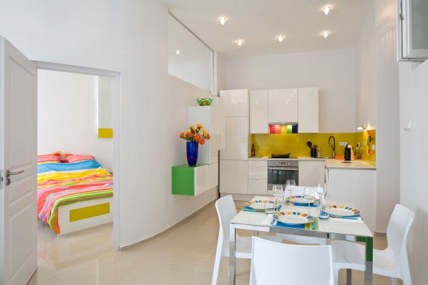 White kitchen with hints of bright colour including yellow and green, with a bedroom behind a curved white wall