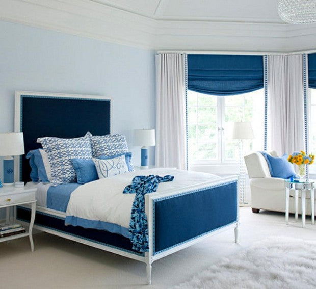 Light blue double bedroom with dark blue used as an accent colour and  dark blue roman blinds in the bay window