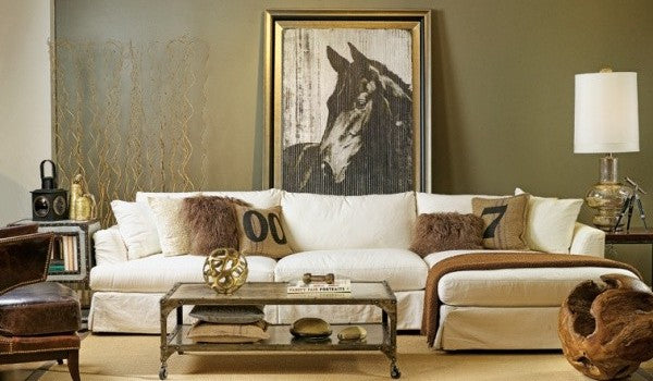 Artistic photo of a horse in black and white in a gold frame, against a dark gold wall