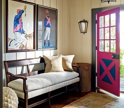 Cream traditional entry halld with a pink wooden door and two paintings of a jockey on the wall