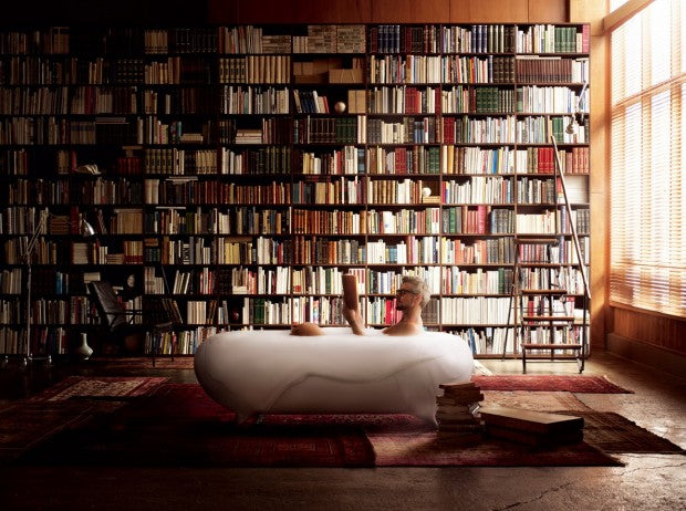 Floor to ceiling bookshelves, with a man in the room sitting in a bathtub reading