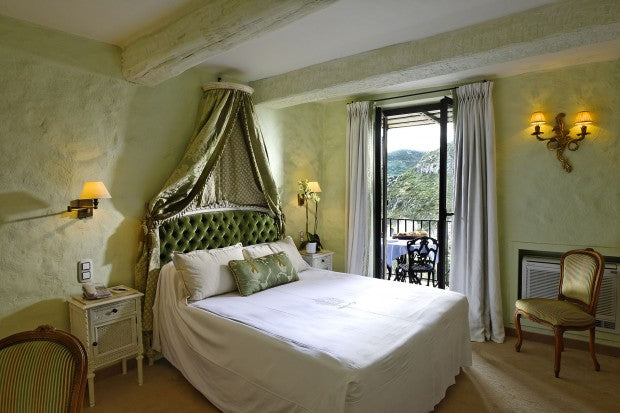 Light green bedroom with white and green bedding, and green canopy over the head of the bed