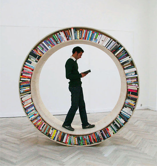 A wooden round 8 foot tall bookshelf that can roll on the floor to access different books, with a man standing inside it like a hamster on a hamster wheel