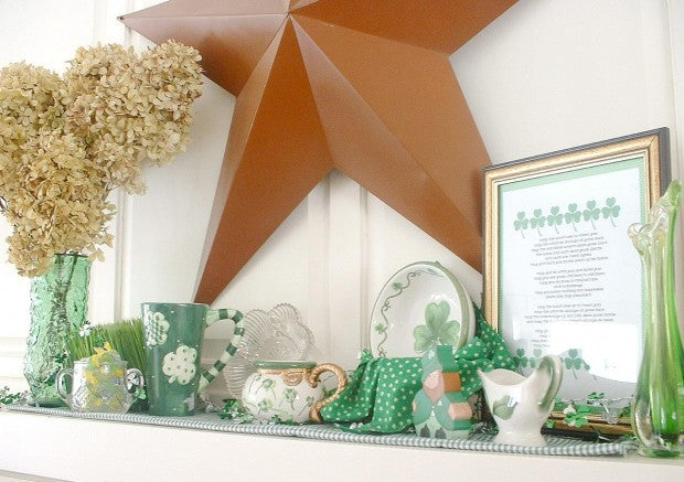 A large brown star ornament and green accessories on a mantle piece