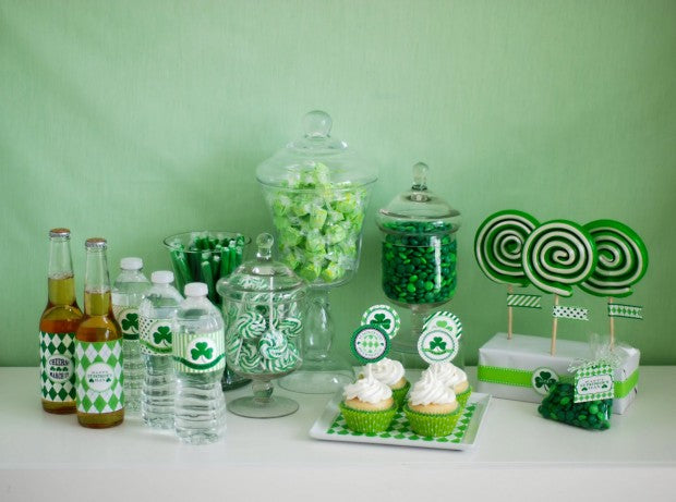 Green sweets, cupcakes and beer bottles in front of a light green wall