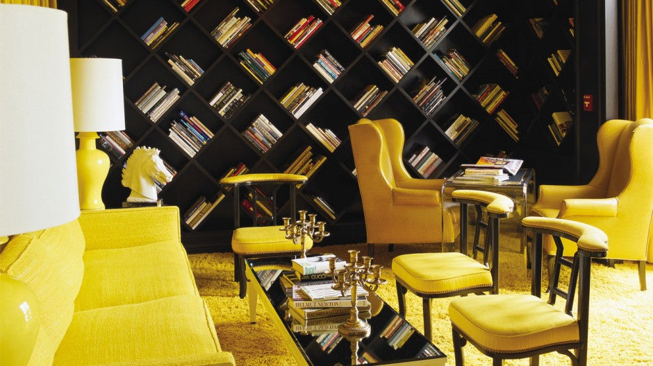 Black and yellow living room with black modular bookshelves that diagonally cross a wall, creating diamond shapes for storing books