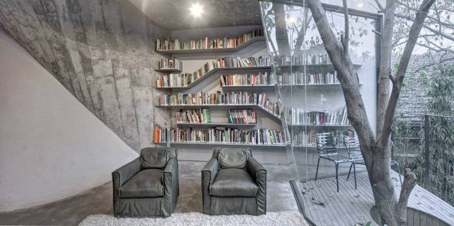 A grey and white reading room with bookselves and a sloping glass window, with decking outside that wraps around a tree