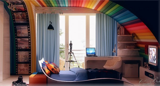 A funky warped single bed under a curved rainbow roof, with a TV at the bottom of the bed