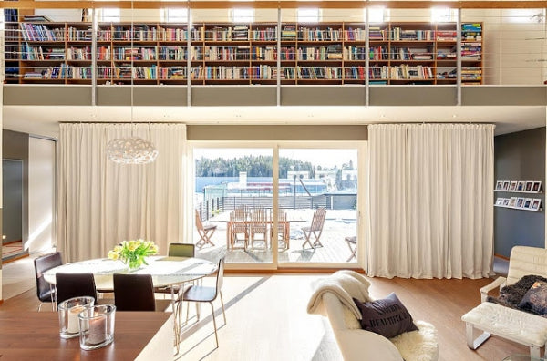 Bright living space with dining table and sitting area, looking out onto wooden decking and garden furniture, with a mezzanine containing bookshelves