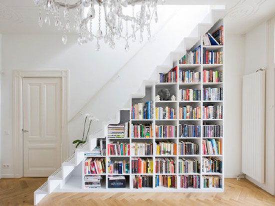 White triangular bookshelves that slope up the side of a white staircase